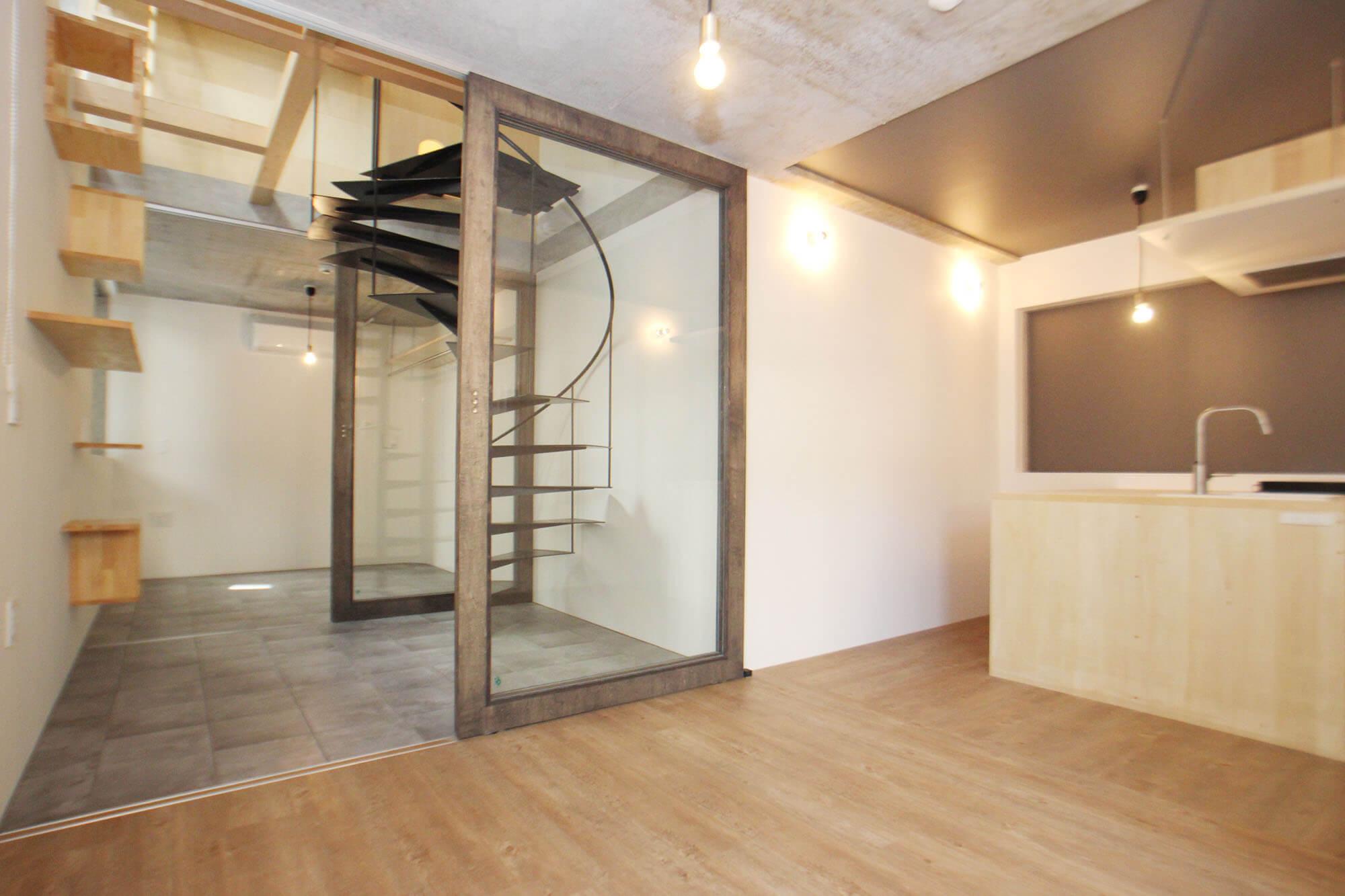 2号室、リビングエリアから見たところ。ガラス越しの螺旋階段とキャットステップがたまりません・・・。ガラスのスライドドアなのでそれぞれのエリアで締め切ることができます。